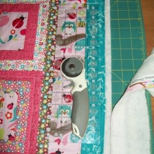 Step 6: the quilt edges are trimmed after machine quilting and before binding.